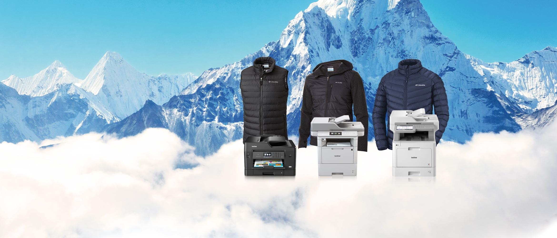 V pozadí hory, tiskárny a bundy