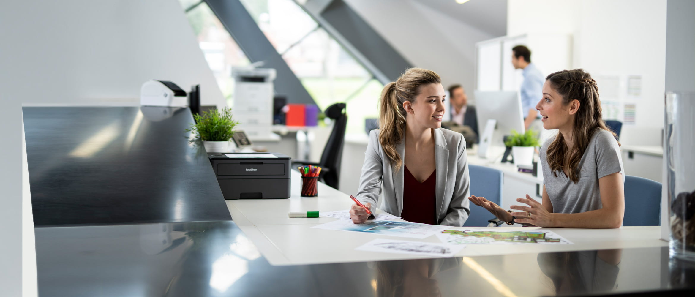 Dvě ženy sedí v rušné kanceláři u stolu a mluví, muži v pozadí, tiskárny, pera a dokumenty