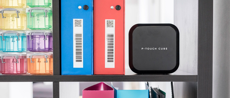 Tiskárna štítků Brother P-touch na polici vedle šanonů se štítky čárových kódů