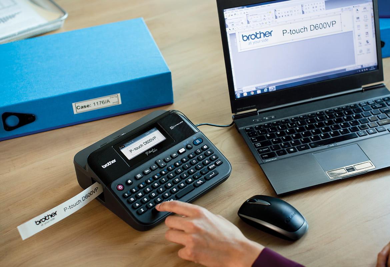 Tiskárna štítků P-touch na kancelářském stole připojená k notebooku tiskne štítek