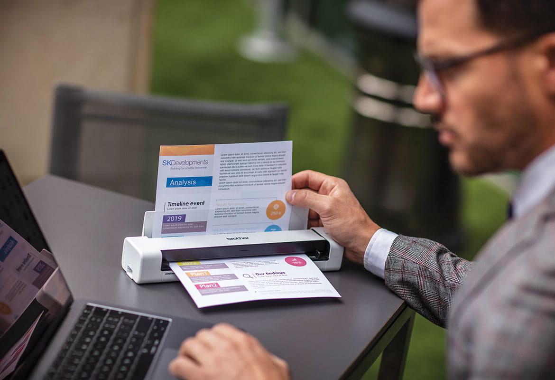 Muž v šedém obleku sedí u stolu s notebookem a skenuje barevný dokument na přenosném skeneru Brother