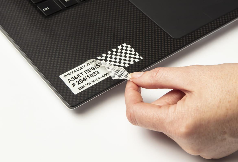 Osoba odstraňuje z notebooku bezpečnostní pásku, šachovnicový vzor dokazuje neoprávněnou manipulaci