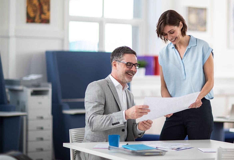 Muž a žena v kanceláři diskutují o dokumentu s laserovou tiskárnou s věžovými zásobníky v pozadí