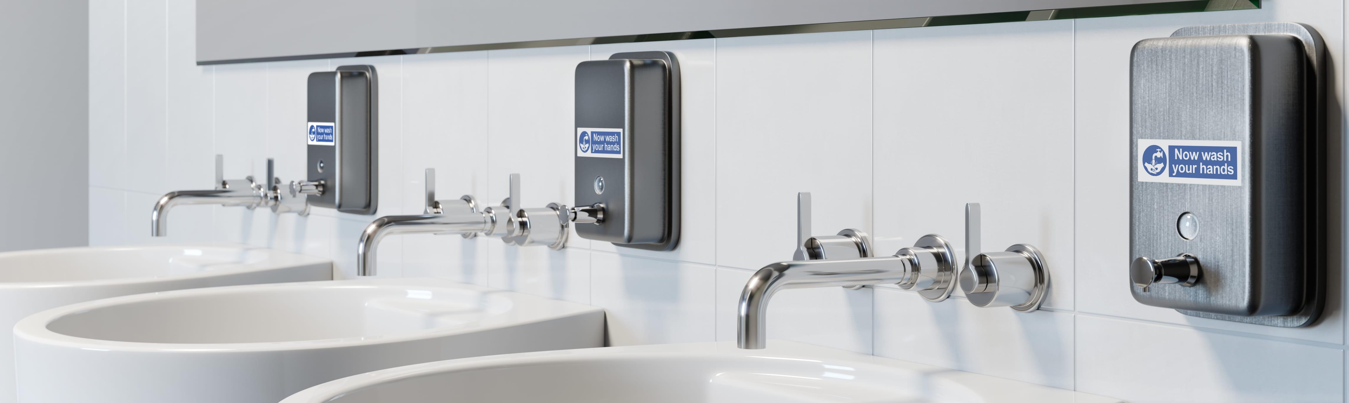 Tři umyvadla v koupelně se štítky p-touch