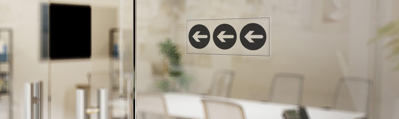 Skleněná kancelářská stěna se šipkou bezpečnostního značení