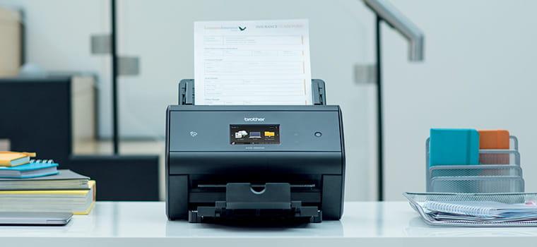 Stolní skener dokumentů Brother ADS-3600W na stole se sešity