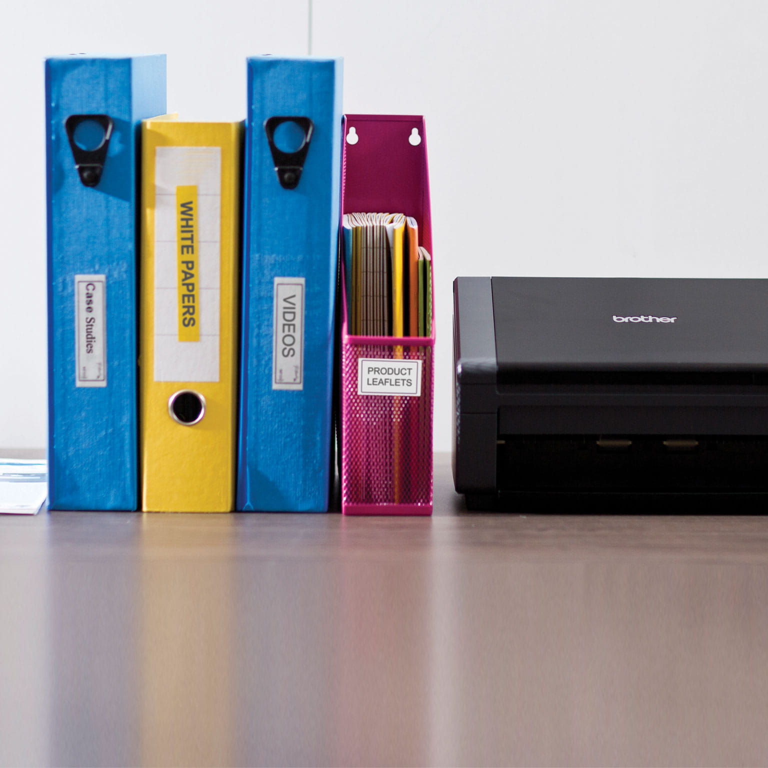 4 folders standing up next to a brother printer