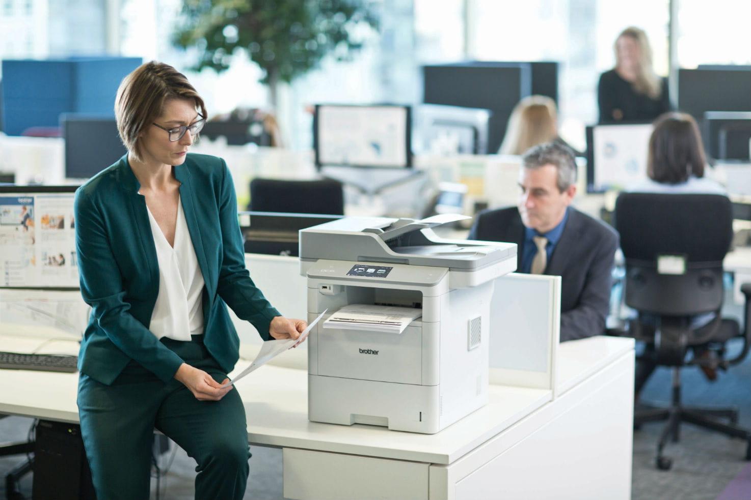 Pracovníci v kanceláři s multifunkční laserovou tiskárnou DCP-L6600DW na stole