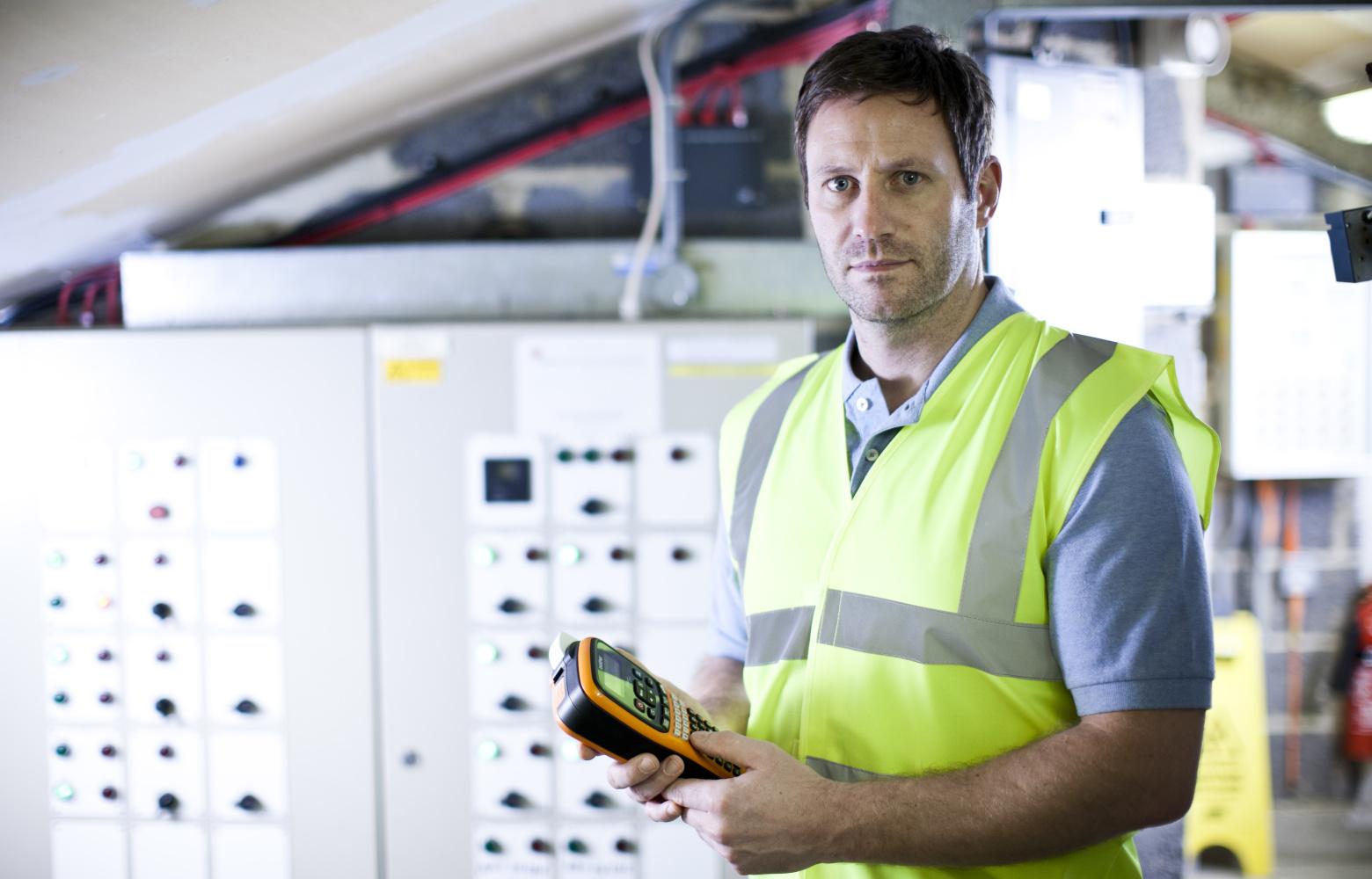 Elektrikář před rozvodnou deskou drží tiskárnu štítků Brother P-touch