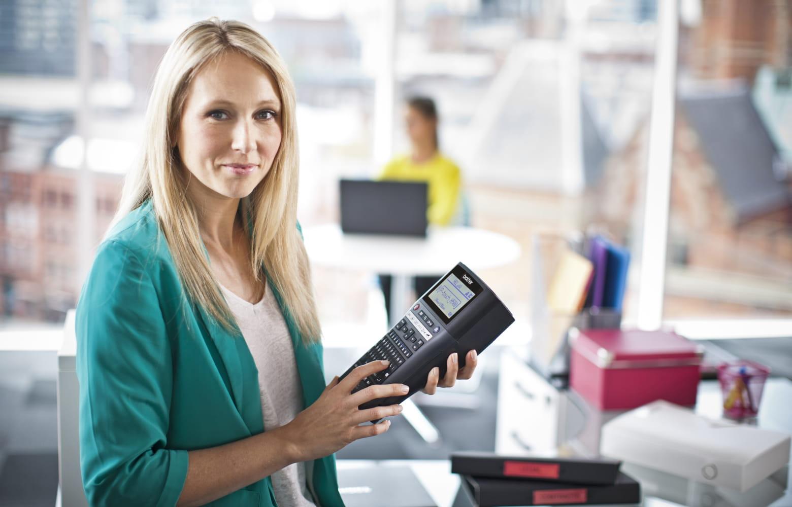 Inventární pracovnice drží tiskárnu štítků Brother P-touch na označování položek v kanceláři