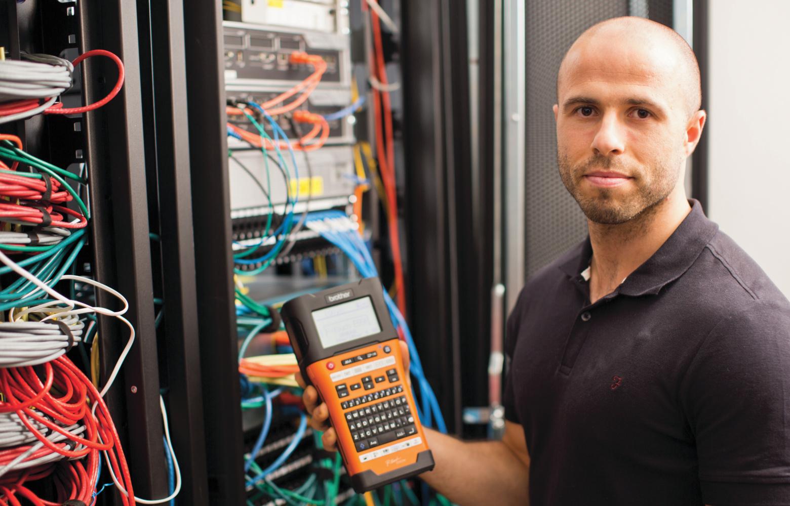 Síťový technik stojí před označenou rozvodnou skříní a drží tiskárnu štítků P-touch