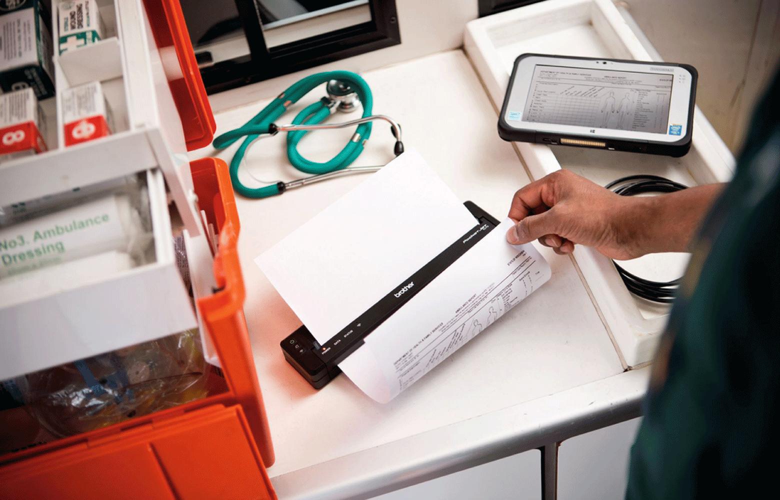 Ambulanční stůl s lékařským zařízením a PJ tiskárna tisknoucí údaje pacienta