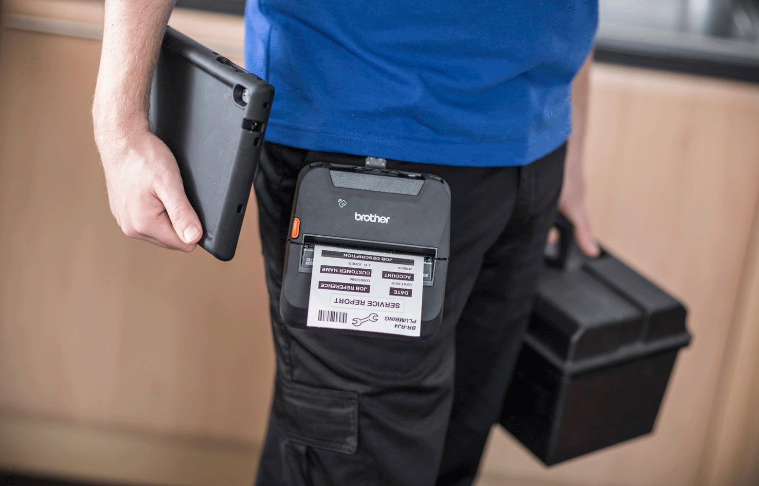 Pracovník v modrém tričku s tiskárnou RJ na opasku drží krabici s nářadím a tablet