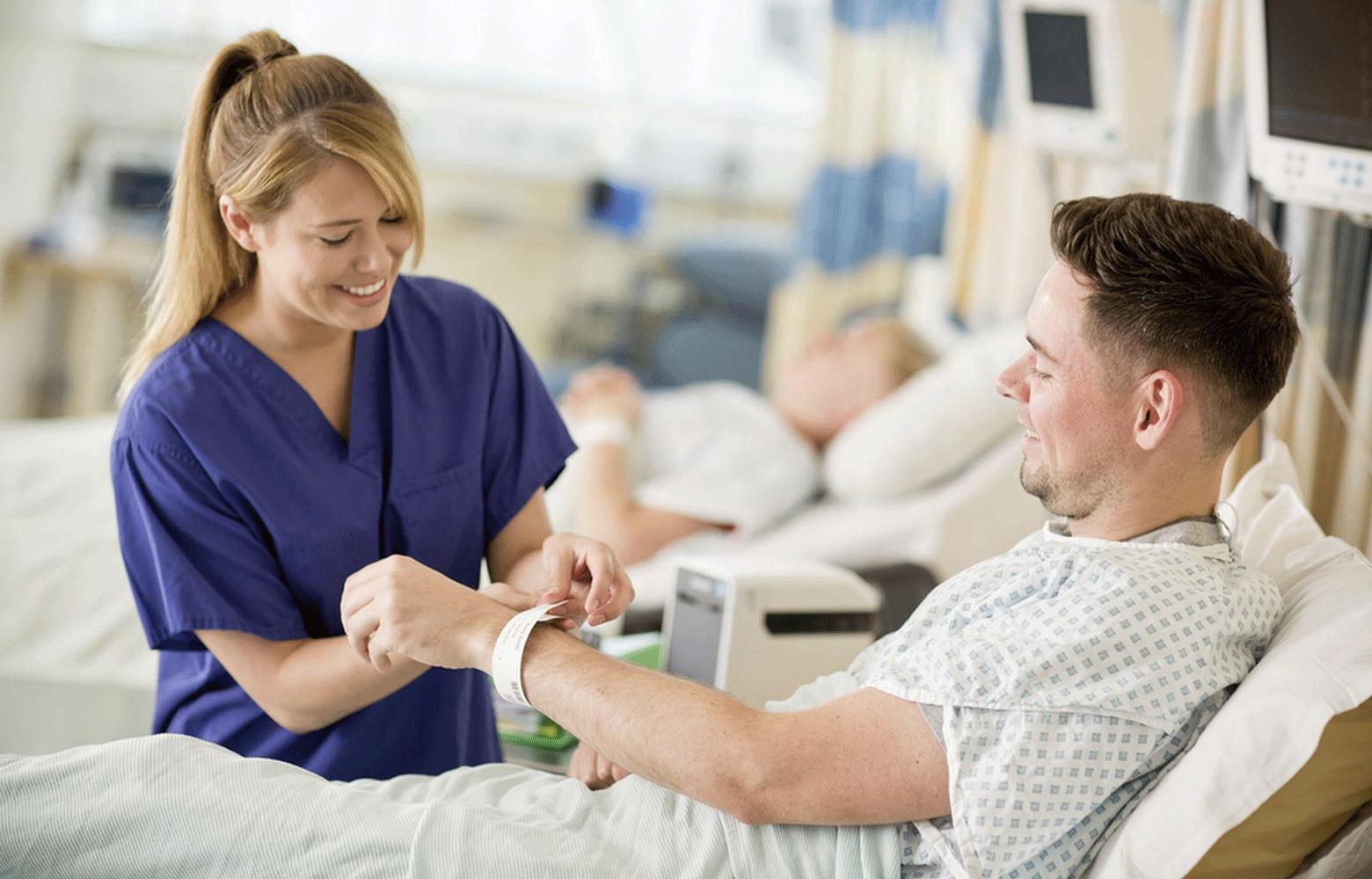 Zdravotní sestra upevňuje identifikační náramek z tiskárny TD na ruku pacienta