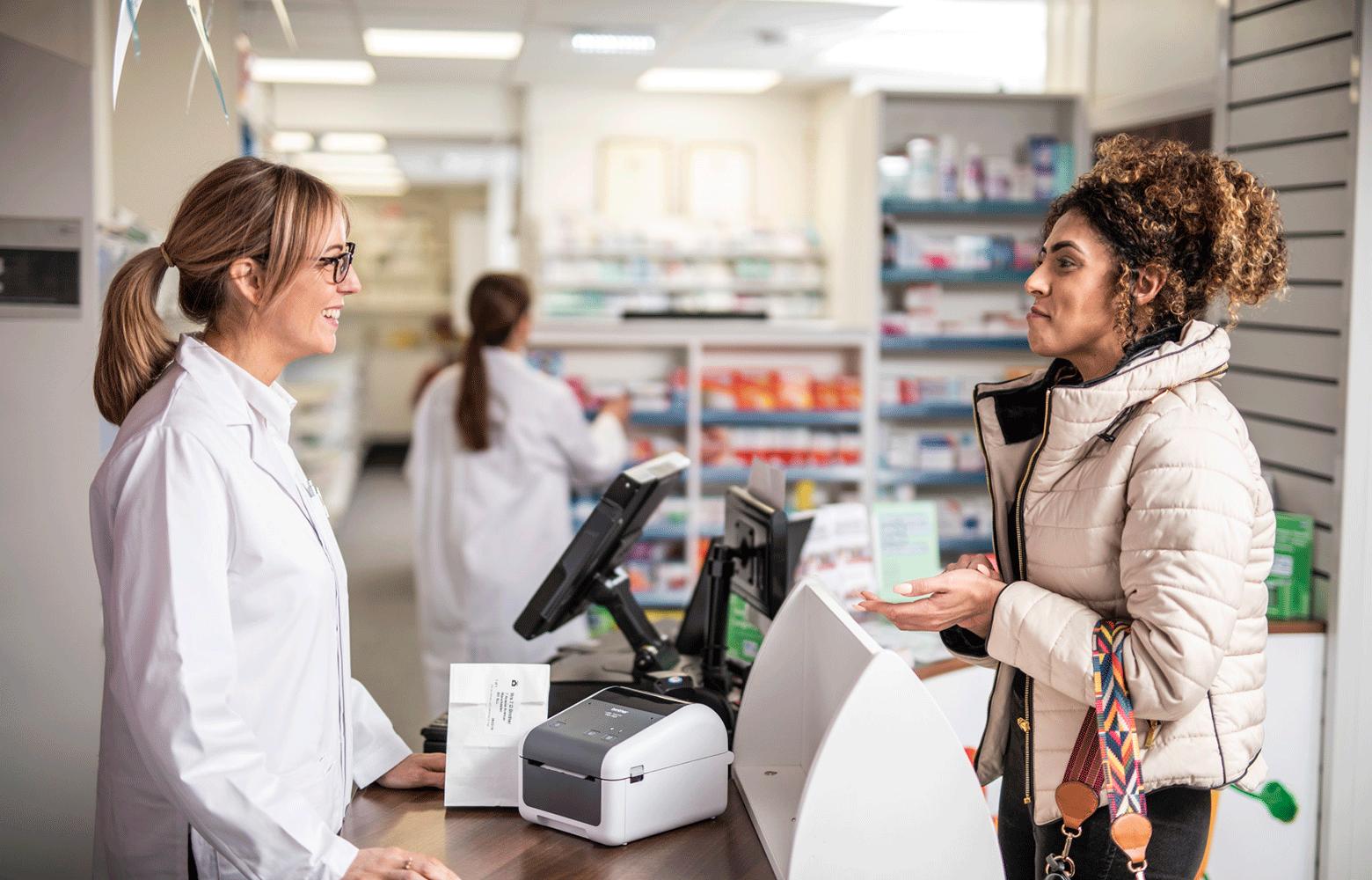 Lékárník u tiskárny štítků na stole mluví se zákaznicí