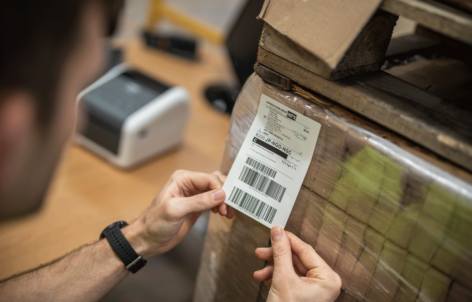 Muž lepí na krabice štítky s popisem doručení