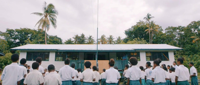 Děti oblečené do uniforem před školou