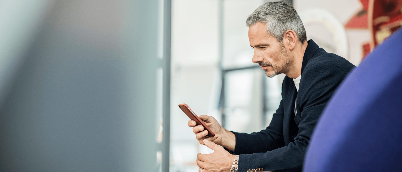 Sedící podnikatel používá v kanceláři mobilní telefon
