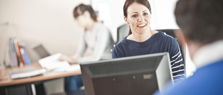 Pracovnice v kanceláři za stolním počítačem se usmívá na kolegu
