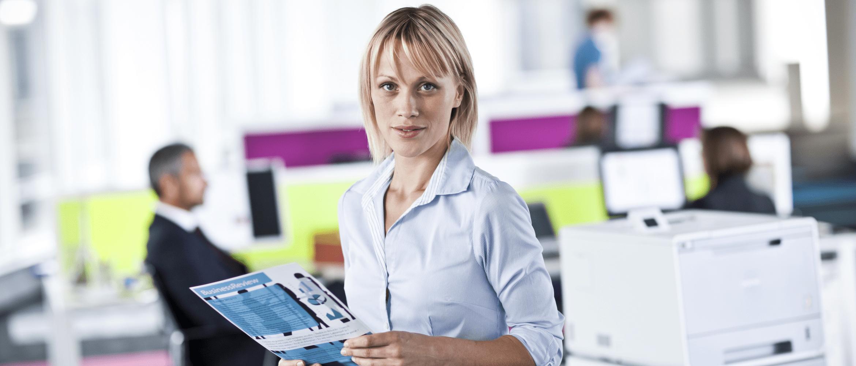 Žena drží výtisk ve velké kanceláři, v pozadí profesionální laserová tiskárna
