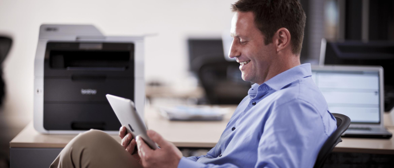 Obchodní pracovník v kanceláři používající tablet, v pozadí notebook a MFC-9300CDW