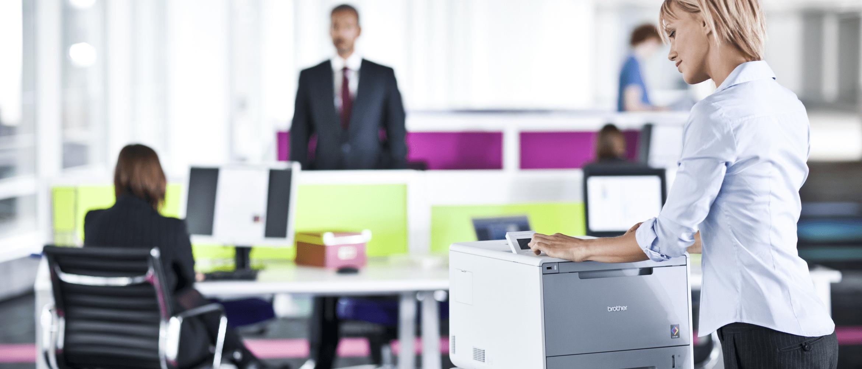 Žena ve vytížené kanceláři se přihlašuje na dotykovém displeji HL-L9200CDWT