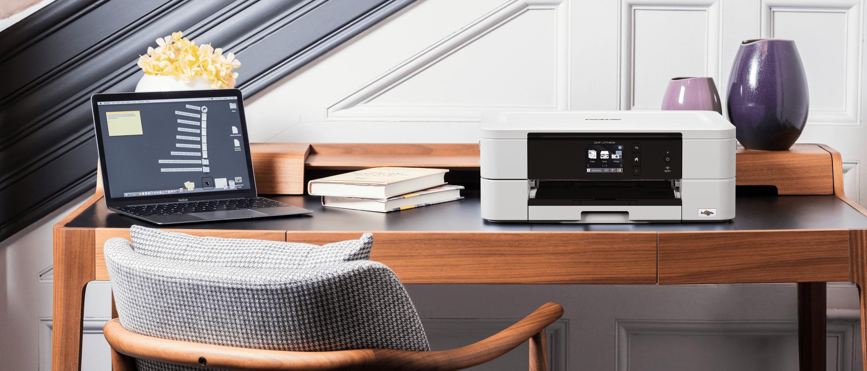 Inkoustová multifunkční tiskárna DCP-J774DW na stole v domácí kanceláři
