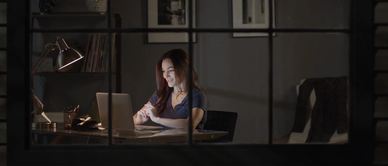 Žena sedí večer za stolem s notebookem