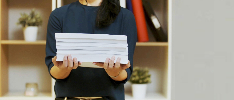 Žena držící stoh papíru
