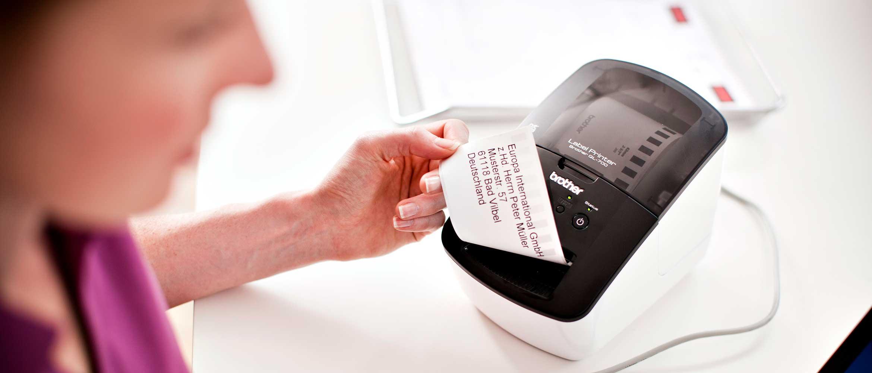 Žena odstraňující štítek z tiskárny štítků Brother QL