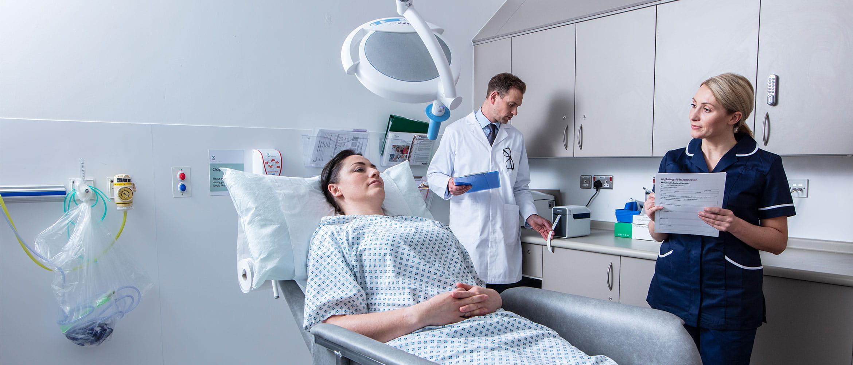 Pacientka položená v ošetřovně, lékař v bílém plášti stojící vzadu a zdravotní sestra s formulářem