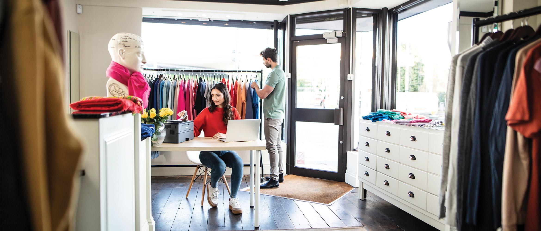 Muž nakupuje oblečení, žena sedí u stolu a tiskne dokument v maloobchodě s textilem