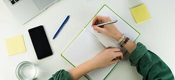 psaní poznámek na stole a mobilní telefon