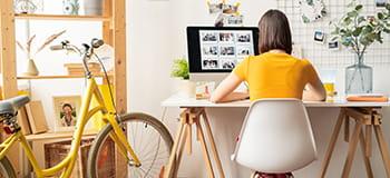 žena sedí u stolu před žlutým jízdním kolem
