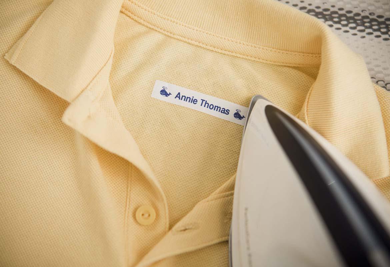 Dětské polokošile označená nažehlovacím štítkem, na kterém je uvedeno jméno dítěte.