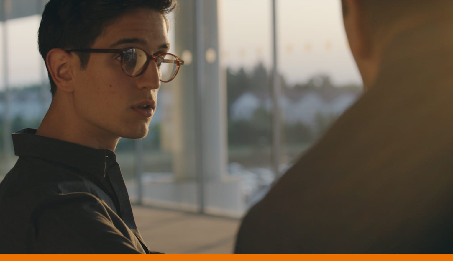 Student with glasses talking with an adult