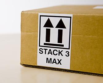Štítek Brother DK vytištěný na tiskárně štítků QL ukazuje, jak stohovat krabice