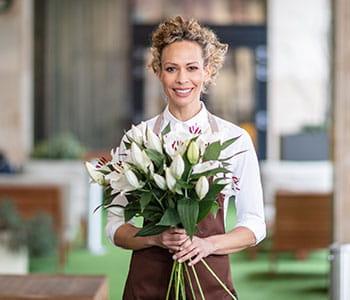 Žena s kudrnatými vlasy svázanými dozadu s hnědou zástěru drží velkou kytici