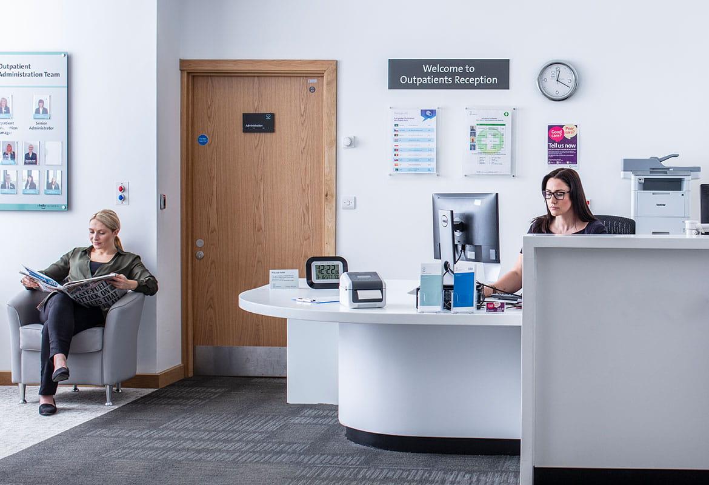 Recepční sedí u stolu s počítačem, sedící pacientka čte noviny