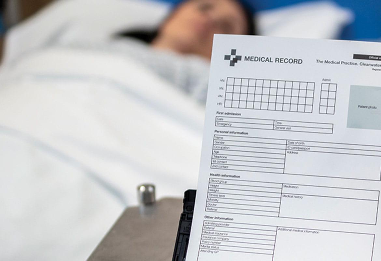 Pacientka leží na posteli, skenování dokumentu pacientky skenerem Brother ADS-3600W