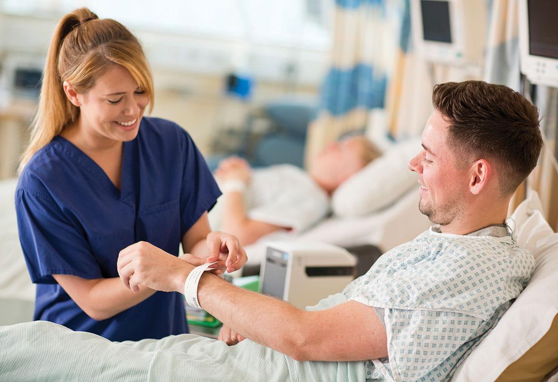 Sestra v modrém plášti připíná ID náramek pacientovi sedícím na posteli