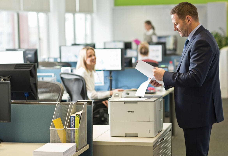 Muž na sobě oblek stojící na tiskárně drží papír, monitory, žena, kancelář, tabulka