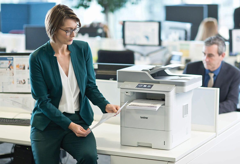 Žena s brýlemi v zeleném obleku stojí u stolu vedle tiskárny Brother MFC-L6900DW, muž v obleku, monitory, stoly