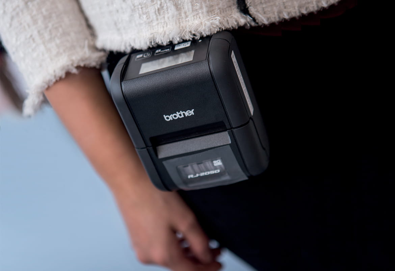 Žena v bílém svetru a černých kalhotách s mobilní tiskárnou RJ-2050