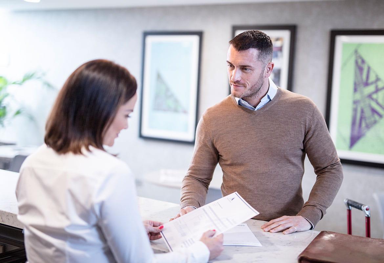 Žena s hnědými vlasy v bílé košili drží papír za stolem služeb zákazníkům, proti ní muž v hnědém svetru s bílou košilí