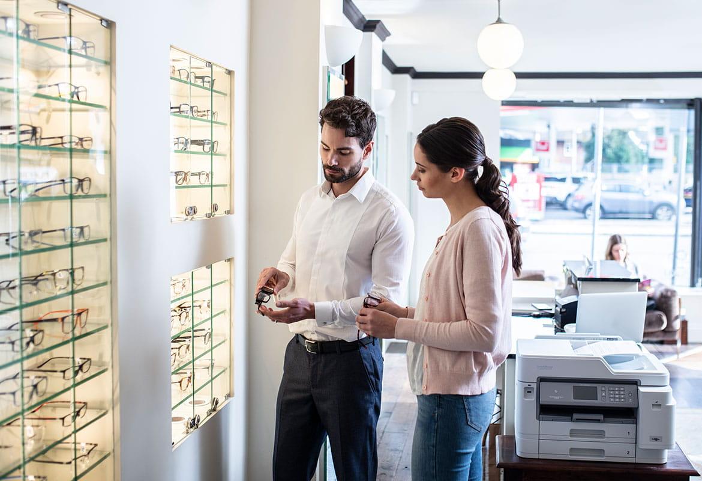 Muž v bílé košili drží brýle, žena s dlouhými hnědými vlasy v copu má na sobě růžový svetr a džíny, Brother tiskárna, brýle, notebook