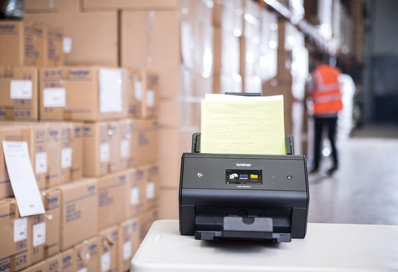 Brother ADS-3600W s expedičními poznámkami ve skladu, pracovník skladu v oranžové pracovní vestě v pozadí, krabice, stůl