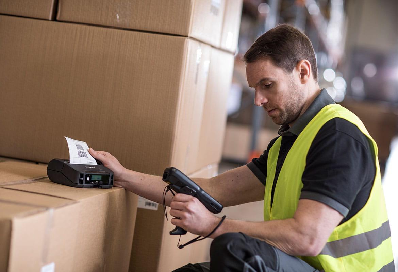 Muž v pracovní vestě drží snímač u tiskárny štítků vedle krabic ve skladu