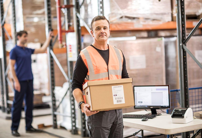 Muž s krátkými hnědými vlasy v oranžové pracovní vestě drží hnědou krabici ve skladu, stůl, monitor, klávesnice, myš, regály