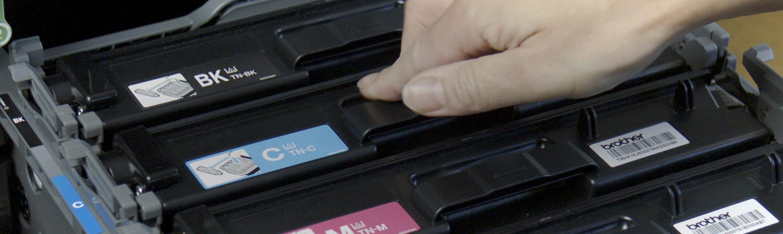 Osoba vkládá tonerovou kazetu do otevřené tiskárny